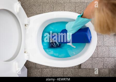 Close-up of a person's hand portant des gants à l'aide de bouteille de détergent toilettes nettoyage Banque D'Images