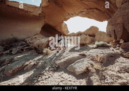 Homme marchant dans le désert avec son vtt vers rock arch, Tenerife, Canaries, Espagne Banque D'Images