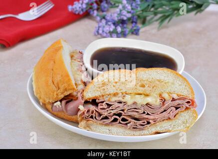 Rôti de bœuf délicieux sandwich dip avec oignons, fromage fondu et beaucoup de sauce. Banque D'Images