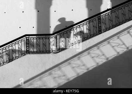 Escalier avec rampe en noir contre mur blanc, avec les ombres d'un homme marchant vers le bas. noir et blanc, image Banque D'Images