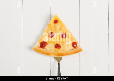 Tranche de pizza sur une fourche sur un fond de bois Banque D'Images