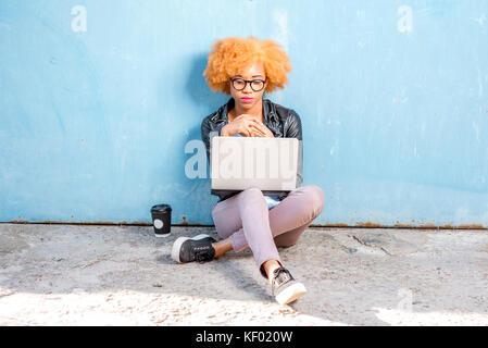 Femme africaine avec l'ordinateur portable sur le fond bleu Banque D'Images