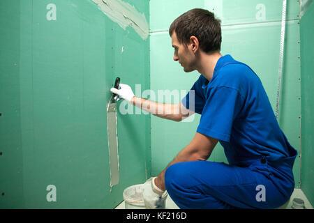 Plâtrier les mains au travail. L'application de l'enduit sur le mur