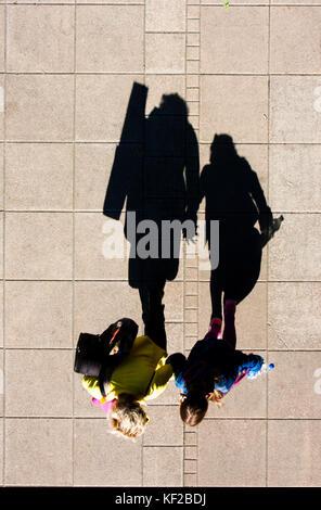 Ombre d'une mère et sa fille marche main dans la main , sur les trottoirs de la ville d'en haut Banque D'Images