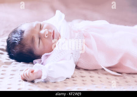 Deux semaines au nouveau-né cute baby girl rose doux vêtements tricotés, dormir paisiblement dans son lit / Naissance Banque D'Images