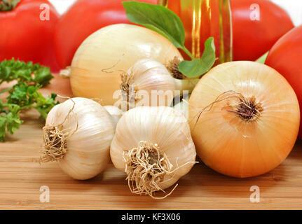 Produits frais du jardin de l'ail, les oignons, les tomates et le persil avec une bouteille d'huile d'olive. selective Banque D'Images