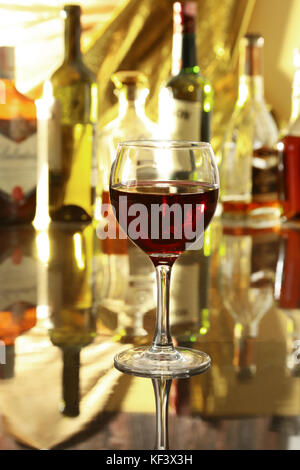 Verre de vin rouge sur la table miroir. bouteilles dans un bar sur l'arrière-plan Banque D'Images