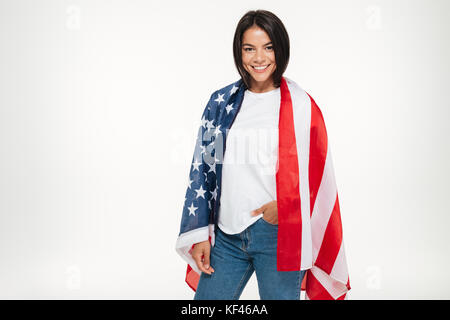 Portrait of smiling young woman wrapped in USA flag and looking at camera isolated over white background Banque D'Images