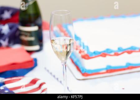 Verre de champagne sur la table avec un gâteau en arrière-plan au rassemblement électoral