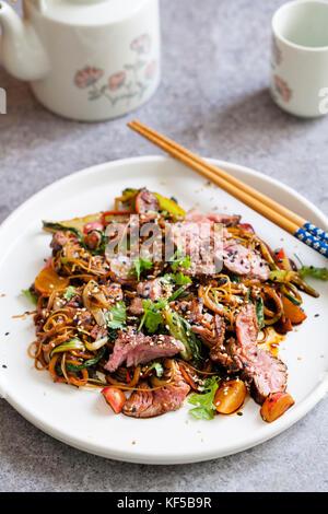 Sauté de filet de boeuf avec courgettes, radis, bok choi et nouilles de riz Banque D'Images