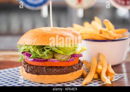Burger de boeuf avec la laitue, les oignons, les cornichons et des tomates Banque D'Images