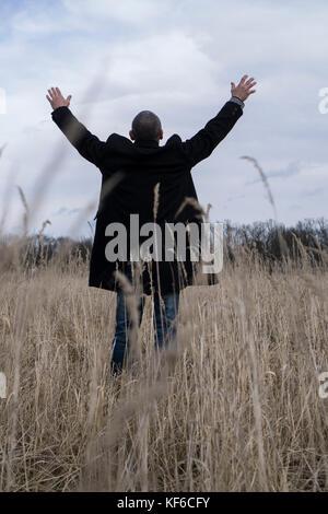Vue arrière d'un homme portant un manteau d'un champ permanent bras tendus