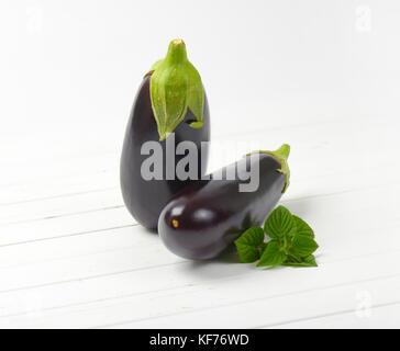 Deux aubergines fraîches et sage sur fond de bois blanc Banque D'Images