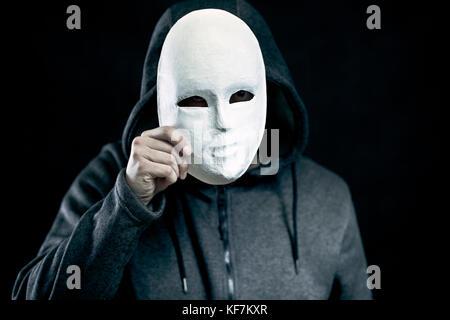Man holding masque blanc pour cacher son visage Banque D'Images