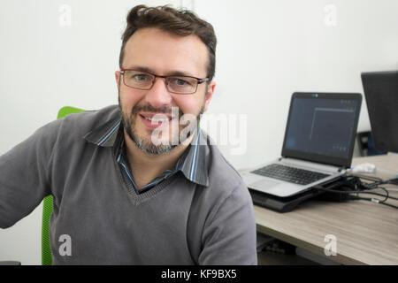 Happy man, développeur de logiciels, technicien en informatique travaillant dans un bureau moderne d'une start up Banque D'Images