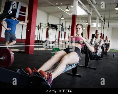 Les femmes utilisant des machines à ramer en salle de sport Banque D'Images