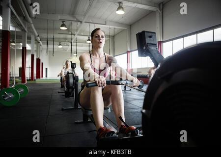Femme déterminée l'exercice sur machine à ramer Banque D'Images