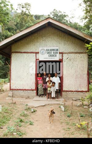 Philippines, Palawan, barangay région, un prédicateur de batak et sa famille se tenir en face de l'église qu'ils Banque D'Images