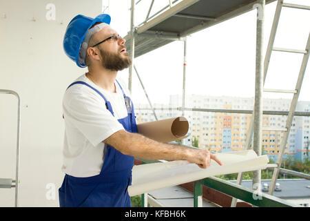 Travailleur de la construction dans une tenue de travail et dans un casque est située à une altitude élevée sur un site de construction avec des plans dans ses mains et montre un doigt pour th