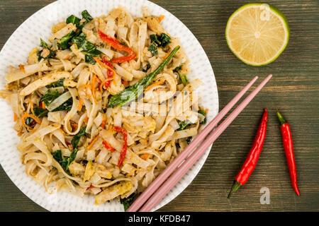 Le style thai pad Thaï au poulet avec des nouilles sur un fond de bois vert Banque D'Images