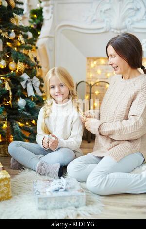 Femme hauts chandail en jeans et tresser les cheveux de sa petite-fille par arbre de Noël Banque D'Images