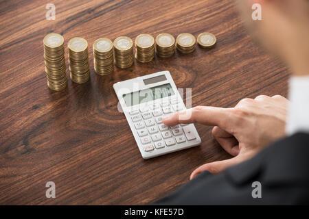 Close-up of businessman le calcul avec la calculatrice en face de pièces empilées à 24 Banque D'Images