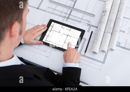 High angle view of male architect using digital tablet sur blueprint in office Banque D'Images