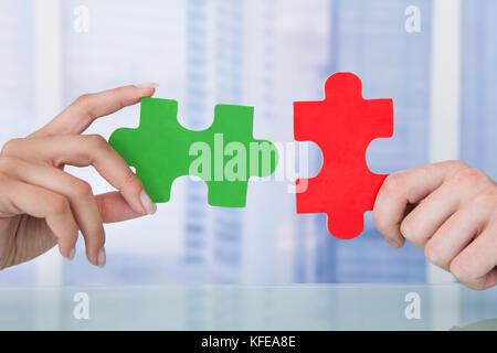 Portrait des gens d'affaires de rejoindre jigsaw pieces in office Banque D'Images