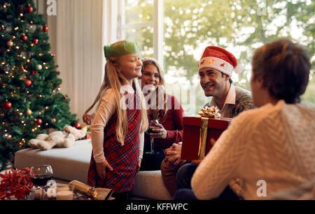 Femme mature en donnant un cadeau de Noël à sa petite-fille. Happy Family in living room la veille de Noël et échange Banque D'Images