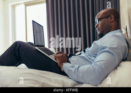 L'homme dans des vêtements formels working on laptop while Lying in Bed. Businessman working on laptop ordinateur Banque D'Images