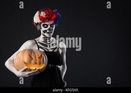 Portrait de femme avec couronne et Scary Halloween maquillage. Zombie dans wreath with pumpkin sur fond noir. Happy Banque D'Images