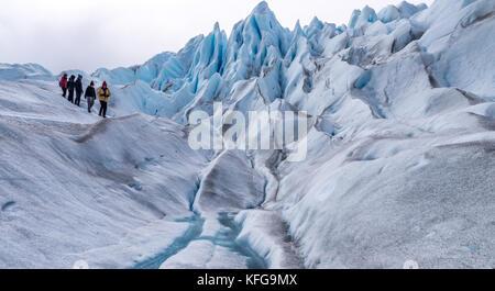Des guides d'un groupe de touristes habillés de couleurs vives sur une courte randonnée glaciaire avec ciel bleu, paysages glaciaires, exécutant des ruisseaux et des pics glaciaires