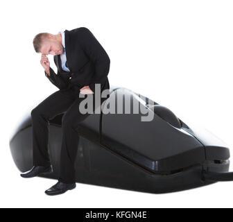 Inquiets businessman sitting on une souris d'ordinateur avec sa tête dans sa main dans le désespoir de conceptuelle Banque D'Images