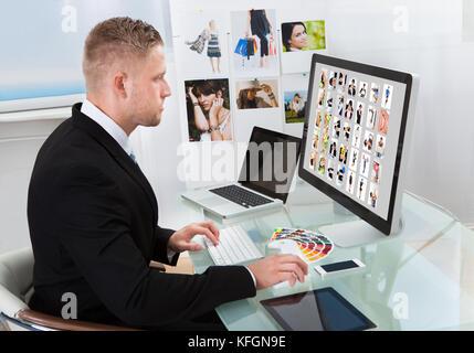 Businessman assis à son bureau en face d'un moniteur à grand écran photographies édition Banque D'Images