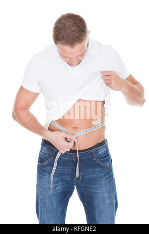 Homme debout la mesure de sa taille son t-shirt blanc comme il regarde le ruban de mesure isolated on white Banque D'Images