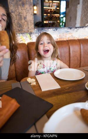 L'âge de quatre ans fille blonde à côté de cris et mère femme assise dans un canapé en cuir brun au restaurant Banque D'Images