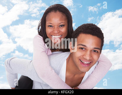 Portrait of happy young man giving piggyback ride to woman against sky Banque D'Images