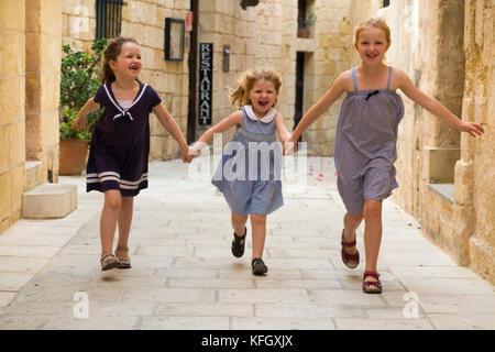 Trois jeunes sœurs / filles / Enfants / Enfants / enfant âgés de 7, 3 et 5 ans, sur des vacances en famille, jouer et courir et span une rue étroite à Mdina, Malte