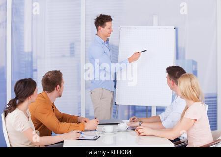 Young businessman giving presentation à ses collègues de l'office de tourisme Banque D'Images
