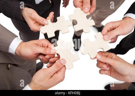 Portrait des gens d'affaires pièces jigsaw fixation sur fond blanc Banque D'Images