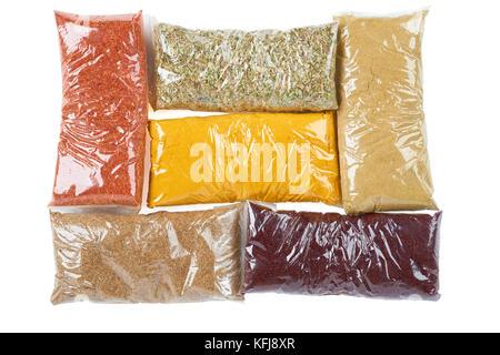 Variété d'épices turc en emballage transparent sur blanc: origan, Indes, cumin, chilly, d'épices pour salade, coriandre Banque D'Images