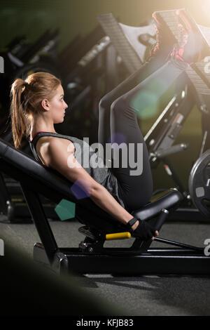 Femme sportive à l'aide de poids Appuyez sur la machine pour les jambes. salle de sport. Banque D'Images
