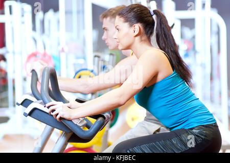 Les gens dans la salle de gym faire du vélo cardio training Banque D'Images