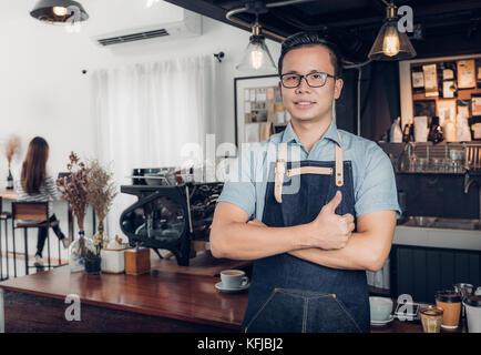Barista mâle Thumbs up in front on cafe bar comptoir avec le client assis à l'intérieur d'un café,bon propriétaire Banque D'Images