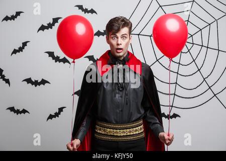 Portrait of handsome young en Vampire costume halloween avec ballon coloré. Banque D'Images
