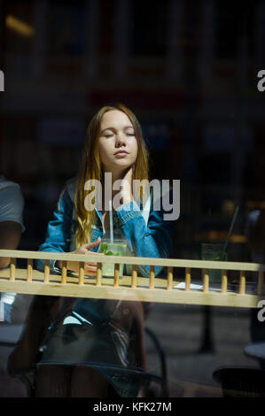 Jolie fille derrière le verre de café. sur une petite table il y a un verre à cocktail. girl pensivement regarde Banque D'Images