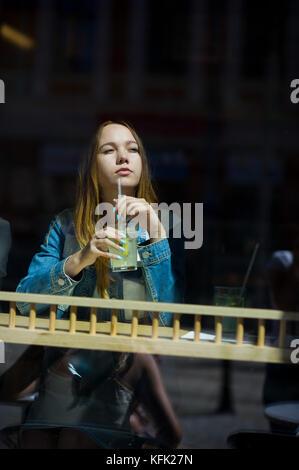 Jolie fille derrière le verre de café. dans une main à la jeune fille un verre à cocktail. elle pensivement regarde Banque D'Images