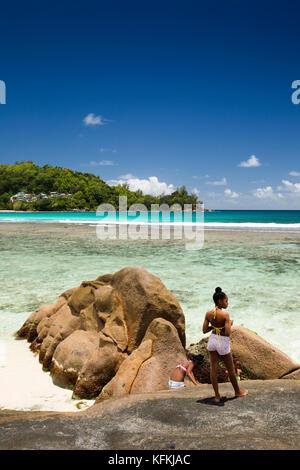 Les Seychelles, Mahe, Baie Lazare, sur la plage, les filles sur les roches de granit pittoresques sculptés par la Banque D'Images