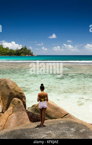 Les Seychelles, Mahe, Baie Lazare, sur la plage, des fille sur les roches de granit pittoresques sculptés par la Banque D'Images