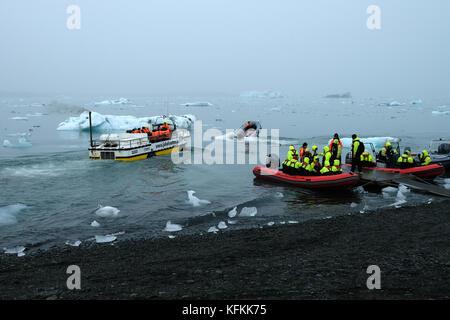 Les touristes en zodiac bateaux de quitter le rivage sur jokulsarlon glacial lagoon d' affichage des icebergs portant Banque D'Images